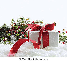 Gift box with red ribbon in snow on white