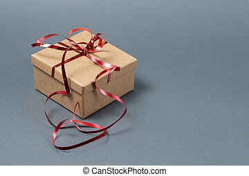 Gift box with red ribbon on a gray background