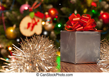 Gift box with red ribbon on festive Christmas background