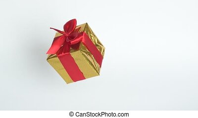 Gift box with red ribbon spinning on white screen. 360 ...