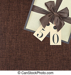 Gift box with ribbon and number 50 on brown background