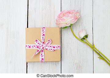 Gift box with ribbon and rose on wooden table for Valentines day