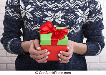 Gift box with ribbon in women's hands.