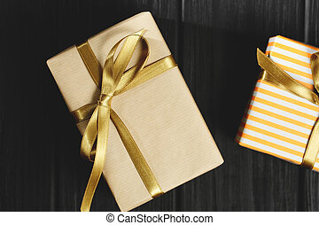 Gift box with ribbon on black wooden background top view.