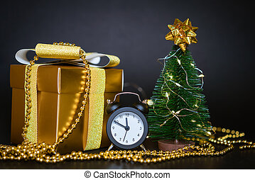gift box with small christmas tree on black background