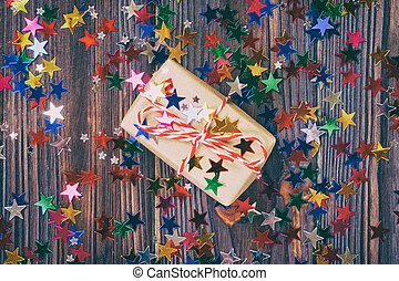 Gift box with star. Creative concept with festive decor on black background. Confetti stars, red, yellow with gift box. Explosion of confetti. Toned