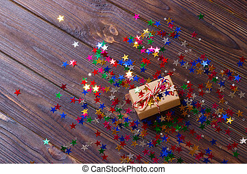 Gift box with star. Creative concept with festive decor on black background. Confetti stars, red, yellow with gift box. Explosion of confetti