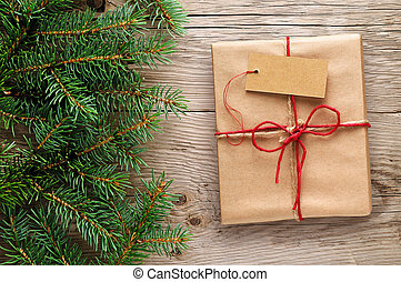 Gift box with tag and fir branches on wooden background