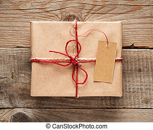 Gift box with tag close-up on wooden background