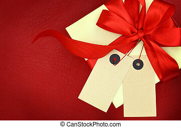 Gift box with two blank tags and ribbon on red background