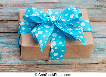 Gift box wrapped in kraft paper with blue ribbon bow on old wood boards with vestiges of blue paint.