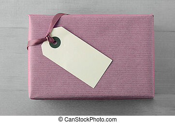 Gift Box Wrapped in Mauve Paper with Blank Tag and Ribbon on Grey Wood Background
