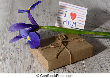 Gift box wrapped with kraft paper, card from child with message for mom and iris flower on gray wood table in morning sunlight. Mother's Day holiday concept.