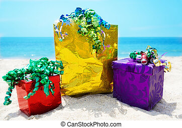 Gift boxes and bag on the beach - holiday concept