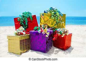Gift boxes and bags on the beach - holiday concept