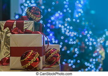 Gift boxes and red balls on table with illuminated Christmas tree