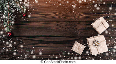Gift boxes over dark wooden background. Top view. Fir tree with baubles, space for text. Effect of light and snowflakes.