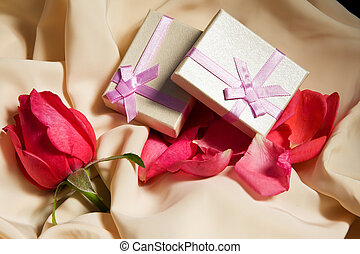 Gift Boxes over satin with rose arrangement.