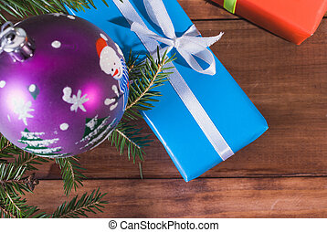 Gift boxes tied with ribbons and Christmas ball under the tree branch