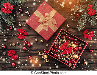 Gift boxes with balls over brown wooden background. Fir tree with baubles, space for text. Top view. Effect of light and snowflakes.
