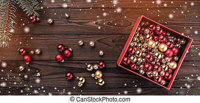 Gift boxes with balls over brown wooden background. Top view. Fir tree with baubles, space for text. Effect of light and snowflakes.