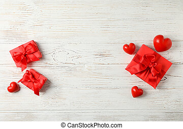 Gift boxes with bow and hearts on wooden background, top view