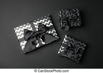 Gift boxes with bow on black background. Black Friday sale