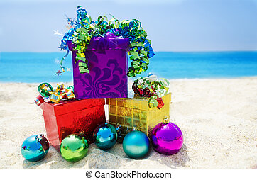Gift boxes with Christmas balls on the beach - holiday concept
