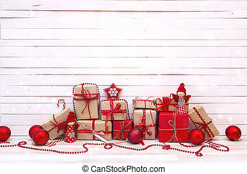 Gift boxes with Christmas decorations on white wooden background.