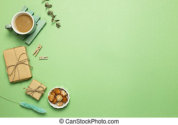 Gift boxes with cup of coffee, dry flowers on green background. flat lay, top view, copy space