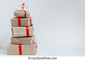 Gift boxes with red ribbons and pine cones on a white wooden table. Christmas background. Space for text. Scandinavian style