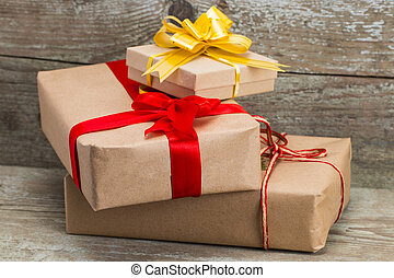 Gift boxes wrapped with kraft paper on wooden background,...