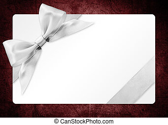 gift card with silver ribbon bow Isolated on red grunge background