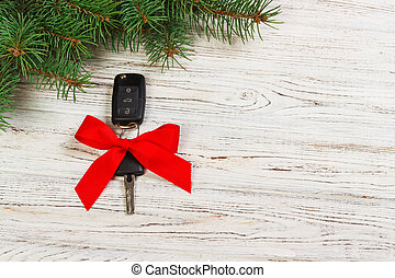 gift for christmas car keys. Close-up view of car keys with red bow as present on wooden background