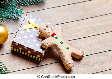 gift, gingerbread man and fir tree branch with bauble on the wonderful brown wooden background