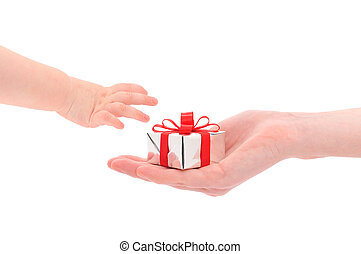 Gift giving - a female hand giving a silver gift box to a ...