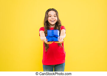 Gift giving makes her happy. Adorable little girl giving blue present box on yellow background. Cute small child enjoy giving the gift. Gift giving occasion