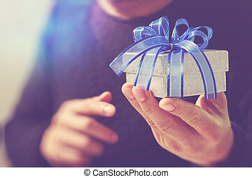 gift giving, man hand holding a gift box in a gesture of giving. blured background, vintage