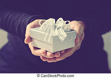 gift giving, man hand holding a gift box in a gesture of giving. blurred background, bokeh effect, vintage