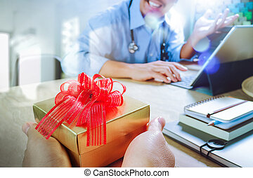 Gift Giving. Patient hand or Team giving a gift to a surprised Medical Doctor in hospital office, filter film effect