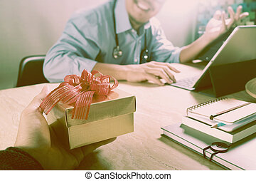 Gift Giving.Patient hand or Team giving a gift to a surprised Medical Doctor in hospital office,filter film effect