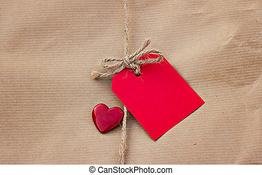 Gift in kraft paper with red card and heart