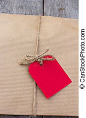 gift in kraft paper with red card