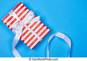 Gift in red and white packing with ribbon