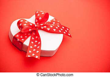 Gift in the form of heart tied with red ribbon with a bow on red