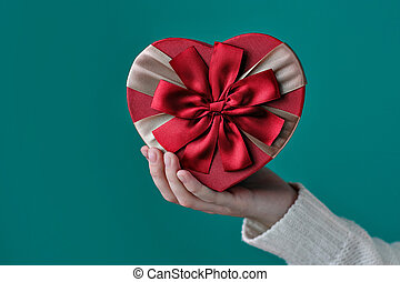 gift in the shape of a heart in his hand