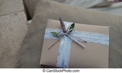 Gift in tissue package with delicate ribbon and flower lies on pillow in room.