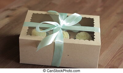 Gift made of recycled carton and  ribbon. Rotation on wood background.