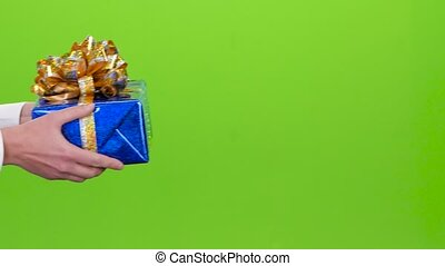 Gift. Man gives a girl the shiny blue box. Studio
