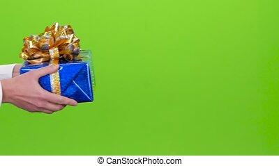 Gift. Man gives a girl the shiny blue box. Studio
